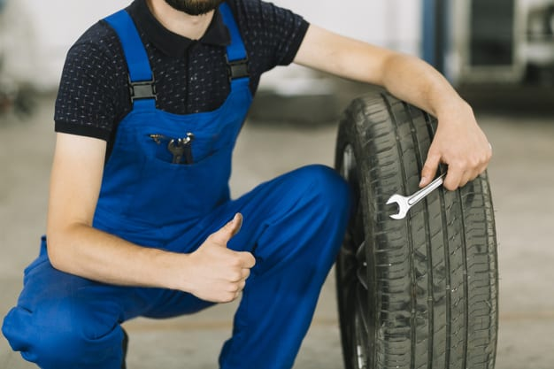 mechanic man with car tire