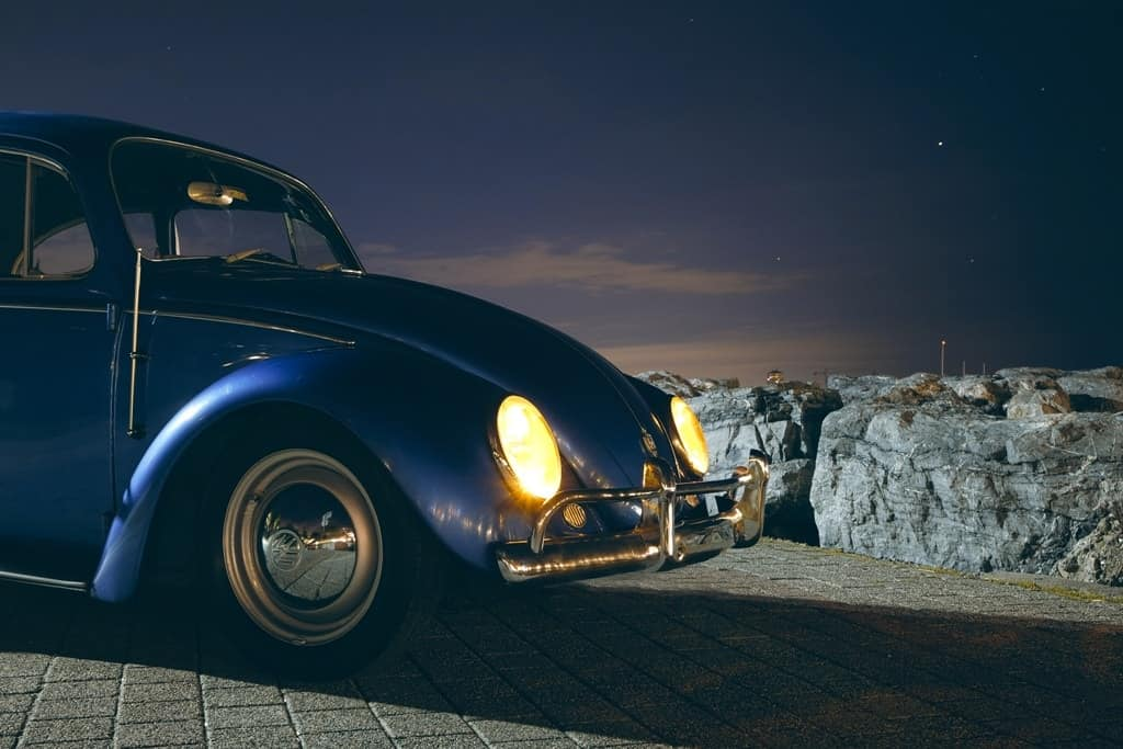 a blue Volkswagen car with lights on during a starry night