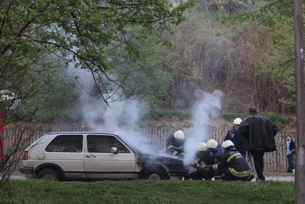 a car with newly burnt front being check by a group of firemen