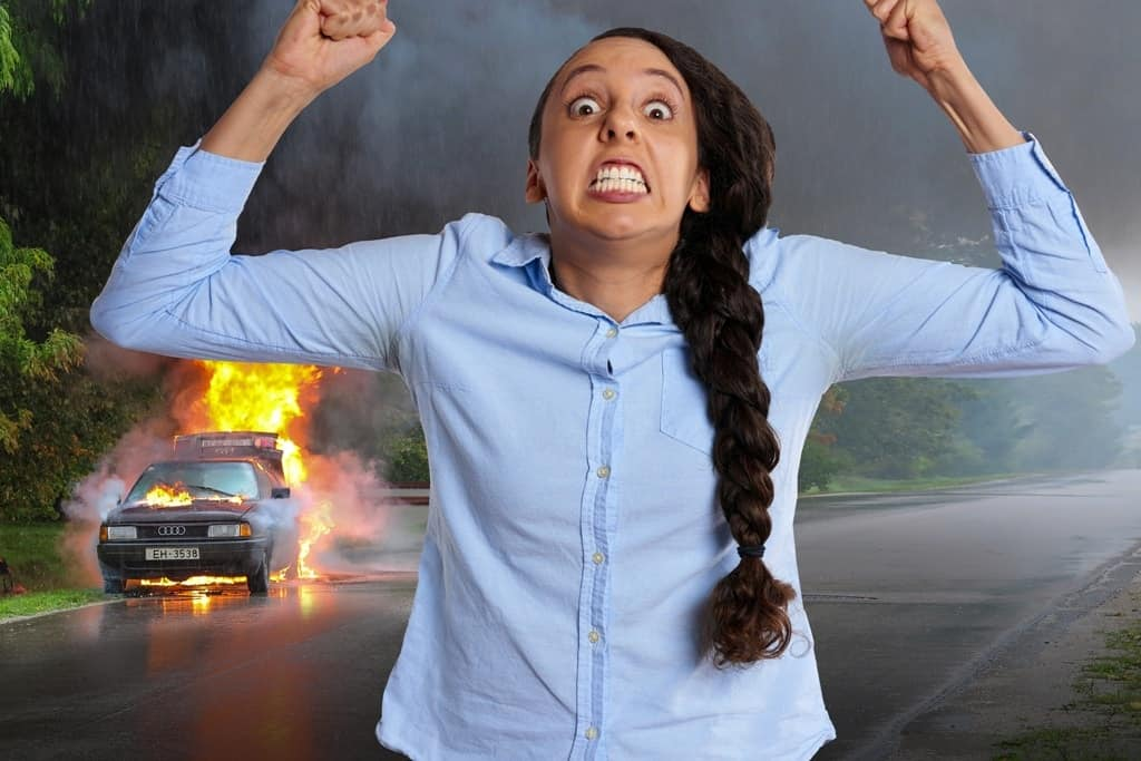 an angry woman with a burning car on her background