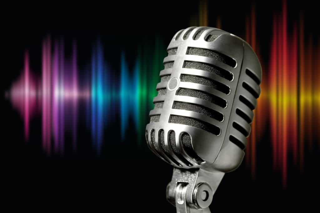 a silver classic microphone with rainbow Sound Waves on its backdrop