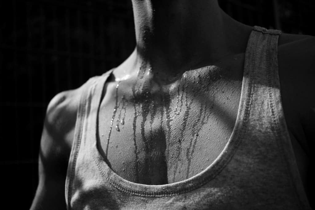 a man sweating a lot that the sweat running from his neck down to his chest