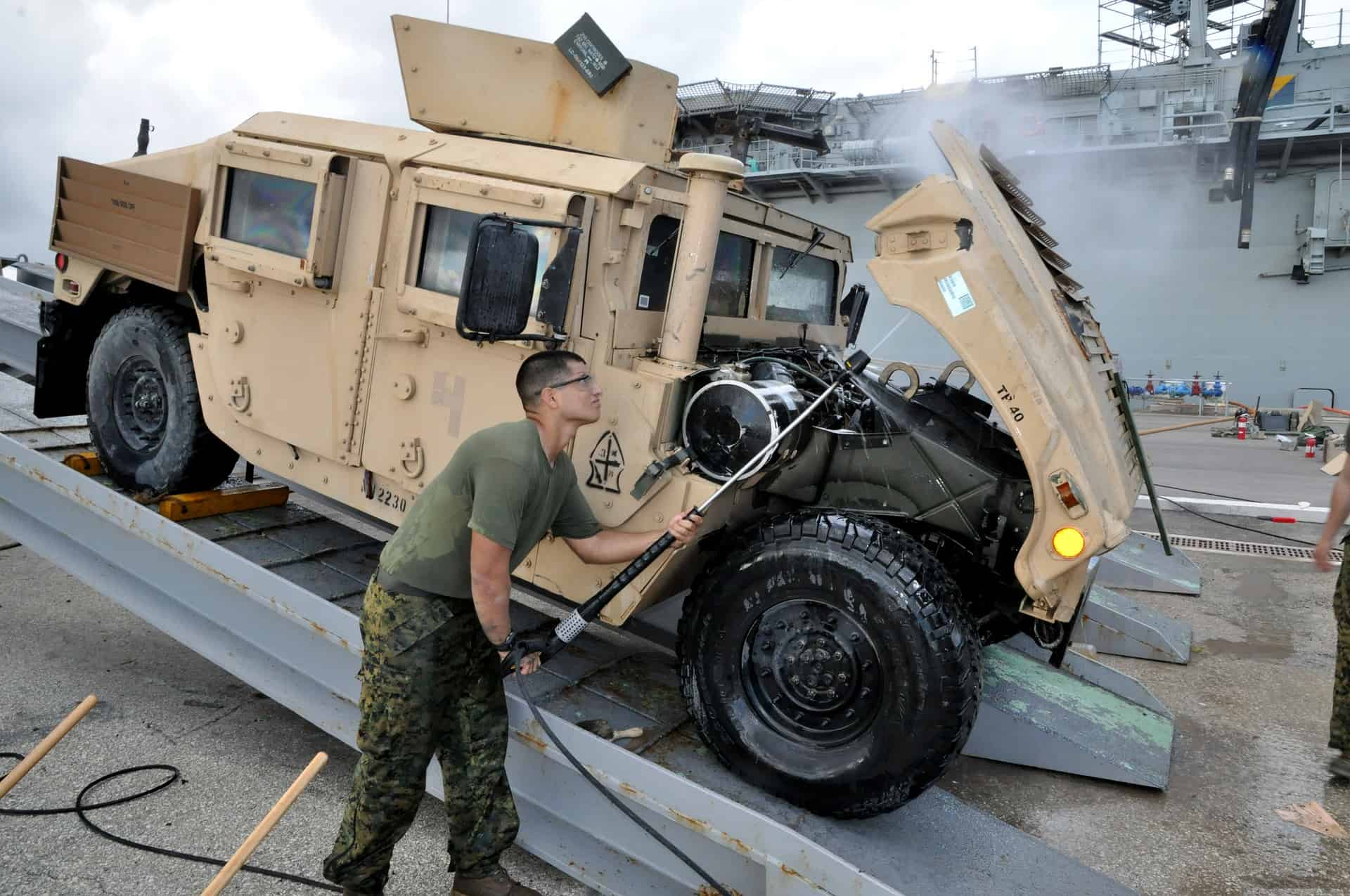 MILITARY GUY cleaning a military vehicle using a pressure washer